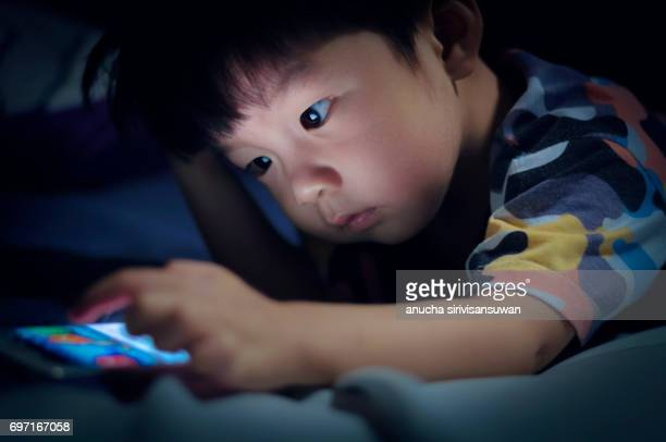 Boy play Telephone  on Bed at night .