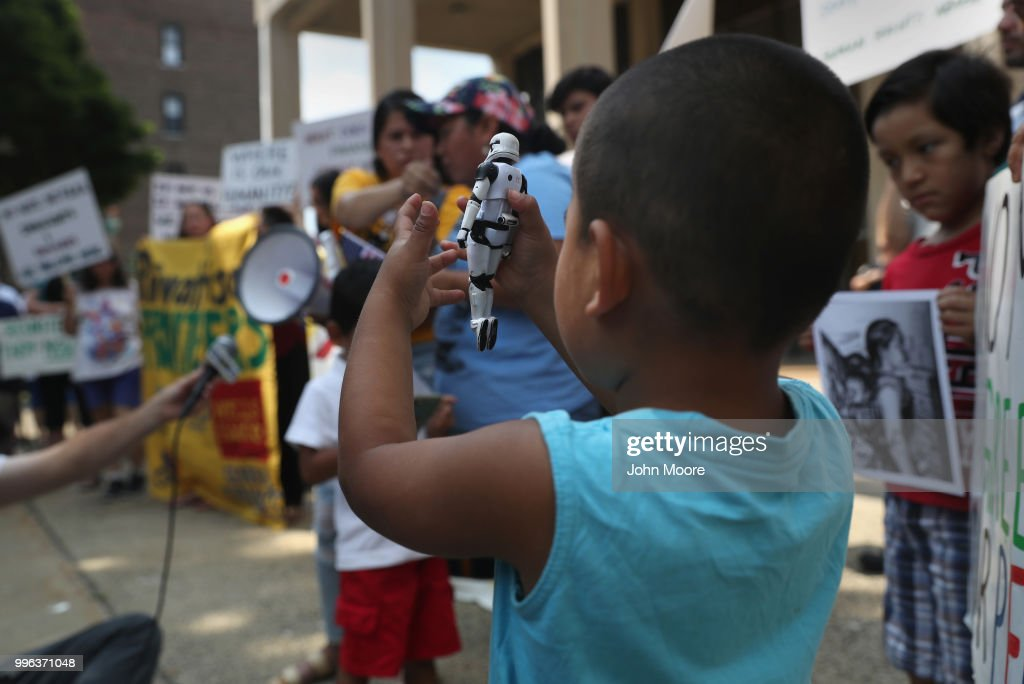 A boy play with a stom trooper toy as his family attends a protest rally against the separation of immigrant families in front of a U.S. federal court on July 11, 2018 in Bridgeport, Connecticut. The rally was in support of two Central American children separated from their parents as a result of the Trump administration's 'zero tolerance' policy on undocumented immigration at the southern border. The two children, who are reportedly being held in a facility in Groton, CT were to appear at a court hearing ahead of possible reunification with their parents.