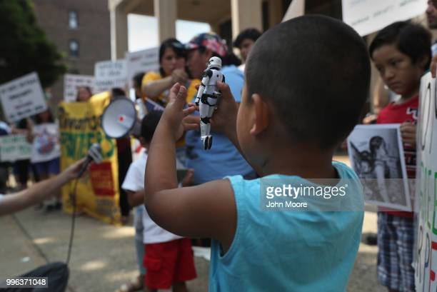 A boy play with a stom trooper toy as his family attends a protest rally against the separation of immigrant families in front of a US federal court...