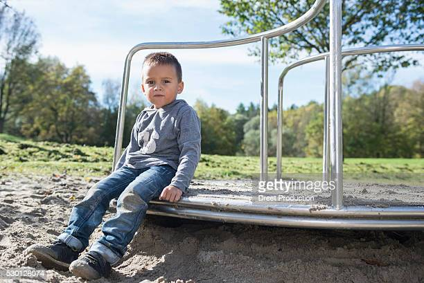 Boy playground sitting portrait sand carousel