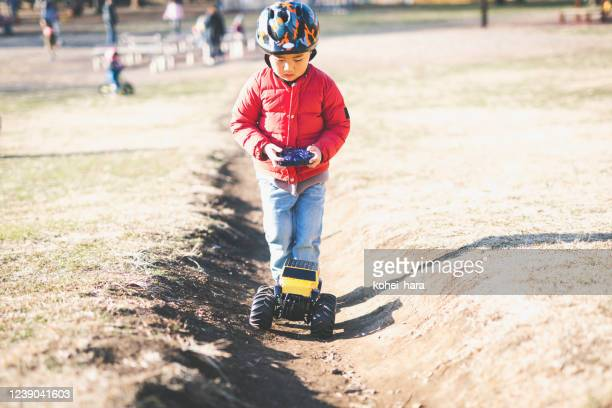 boy playing a radio‐controlled model car in the park - remote control car games stock pictures, royalty-free photos & images