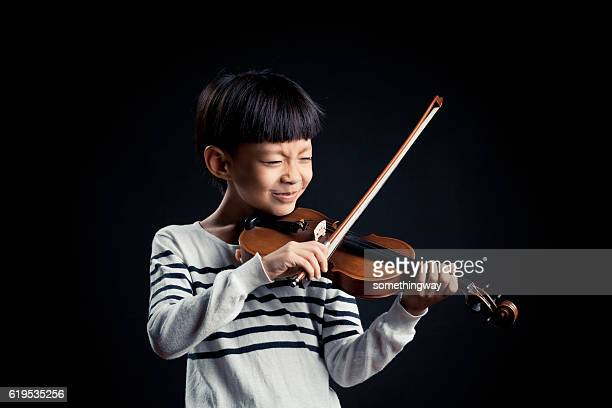 boy playing a Violin isolated over a black background