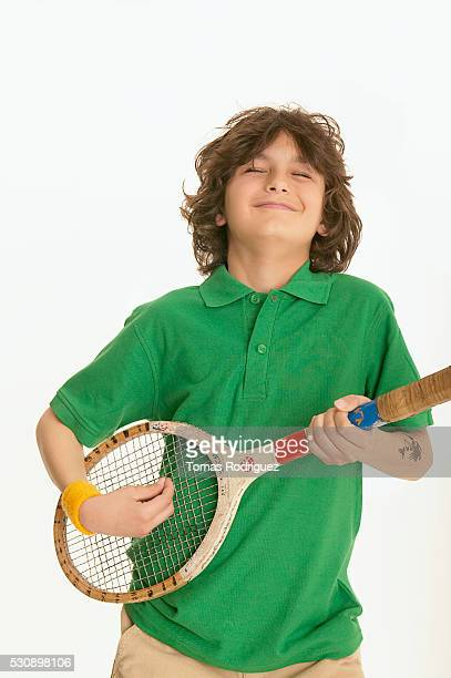 Boy playing air guitar with a tennis racket