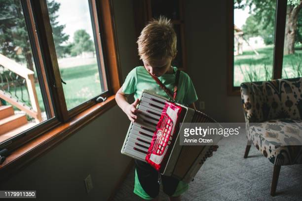 boy playing an accordion - accordion instrument stock pictures, royalty-free photos & images
