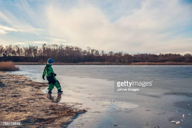 Boy playing at frozen lake