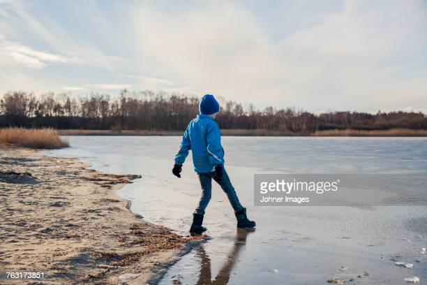 boy playing at frozen lake - mujeres fotos stock pictures, royalty-free photos & images