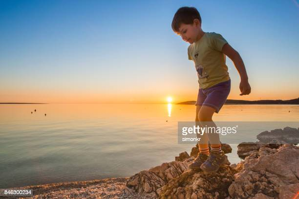 boy playing at the beach - green shorts stock photos and pictures