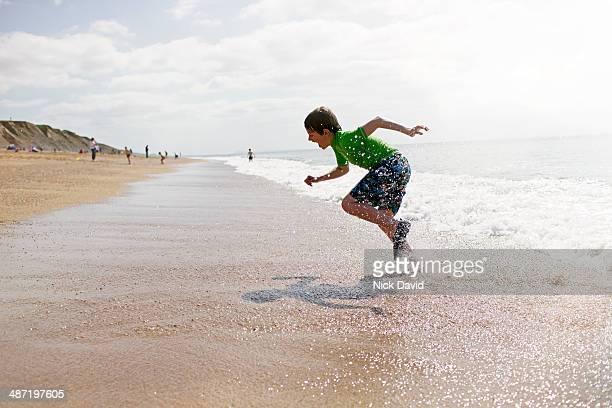 boy playing at the seaside - knaben in badehosen stock-fotos und bilder