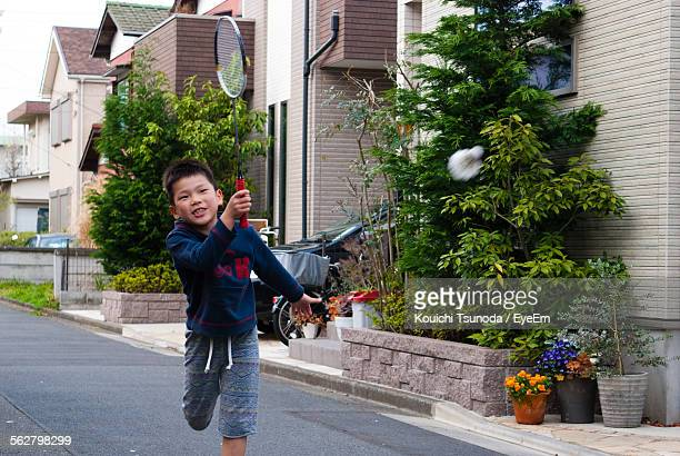 boy playing badminton on street by house - badminton stock photos and pictures