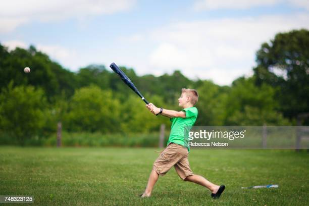 boy playing baseball on field - sports bat stock pictures, royalty-free photos & images