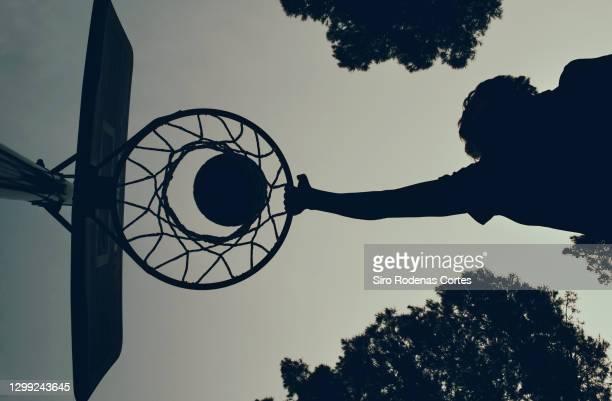 boy playing basketball backlit - encestar fotografías e imágenes de stock