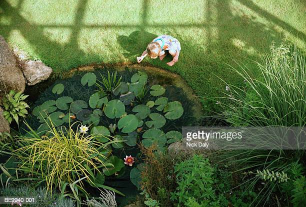 Boy (5-7) playing beside pond, elevated view