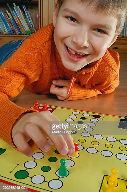 Boy (7-9) playing board game, smiling, portrait