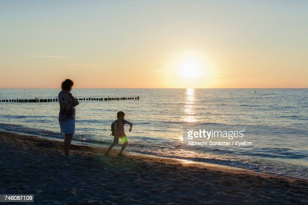 boy playing by woman at beach against sky during sunset - albrecht schlotter fotografías e imágenes de stock