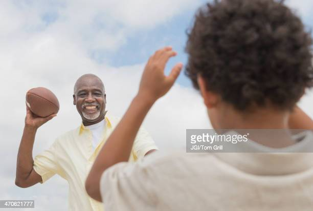 boy playing catch with grandfather outdoors - old american football stock photos and pictures
