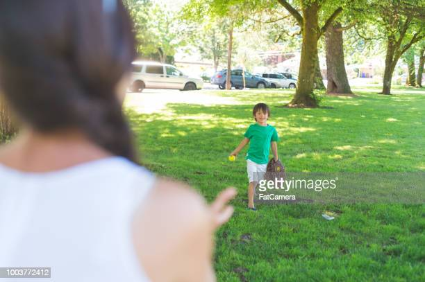 A boy playing catch with his mom at the park