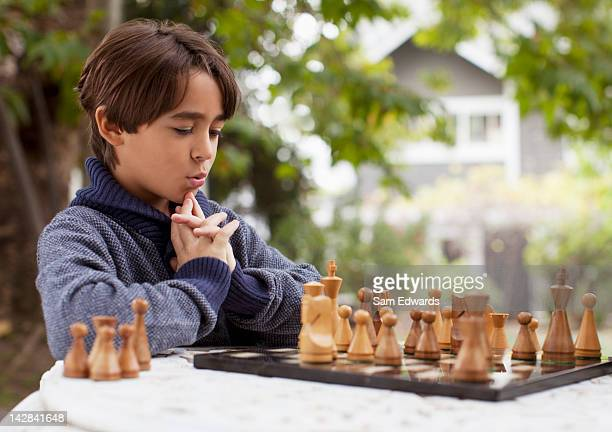boy playing chess outdoors - playing chess stock pictures, royalty-free photos & images