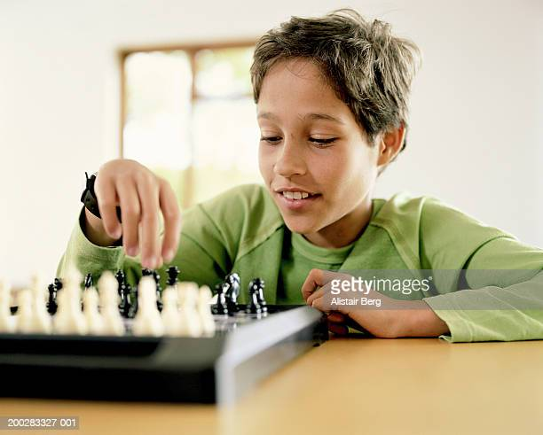Boy (10-12) playing chess, smiling, close-up