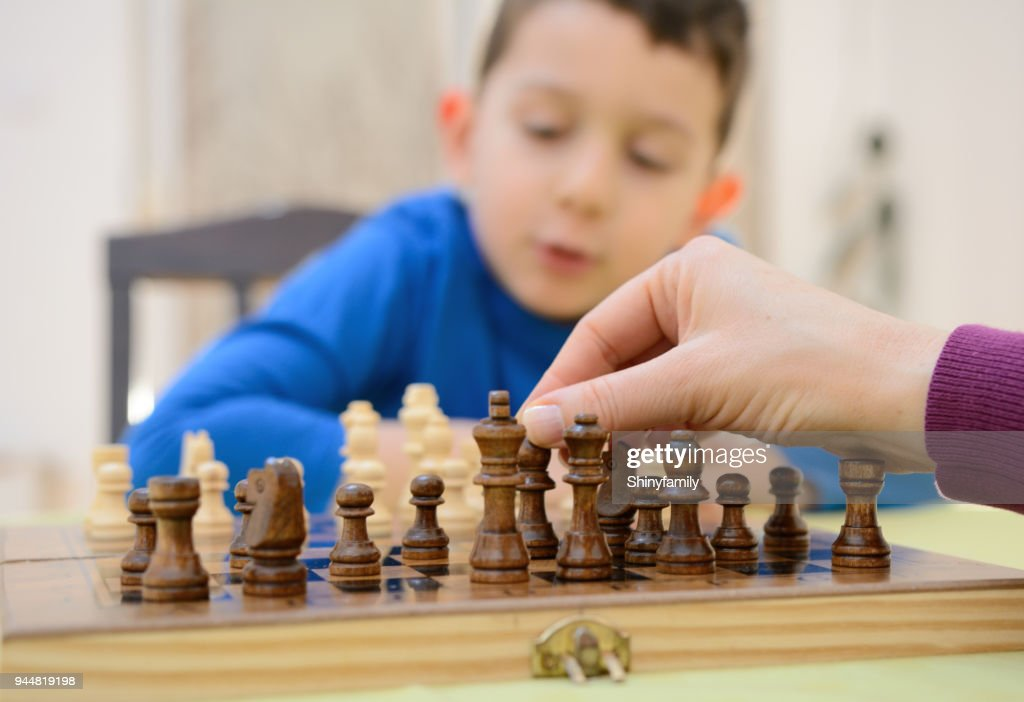 Boy playing chess with mother at home : Stock Photo