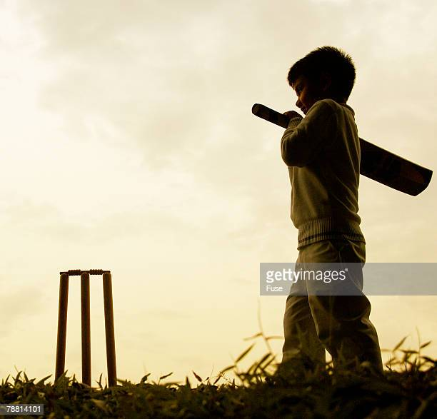 Boy Playing Cricket at Dusk