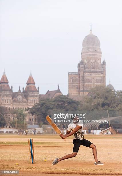 Boy playing cricket at Oval Maidan, Mumbai, India