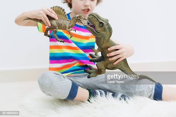 boy playing dinosaur toys