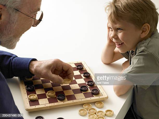boy (5-7) playing draughts with grandfather, close-up - checkers stock photos and pictures