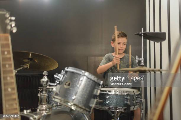 Boy playing drum against wall at home