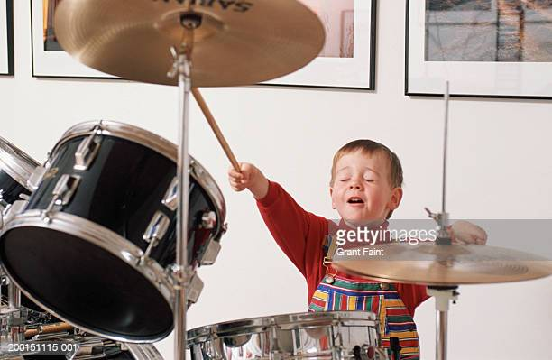 Boy (6-8) playing drums
