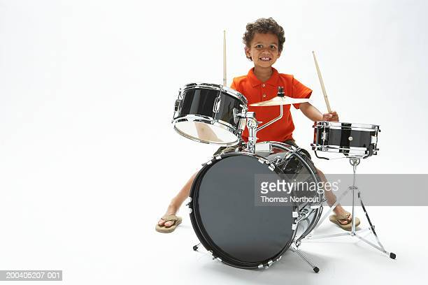 Boy (4-6) playing drums, smiling, portrait