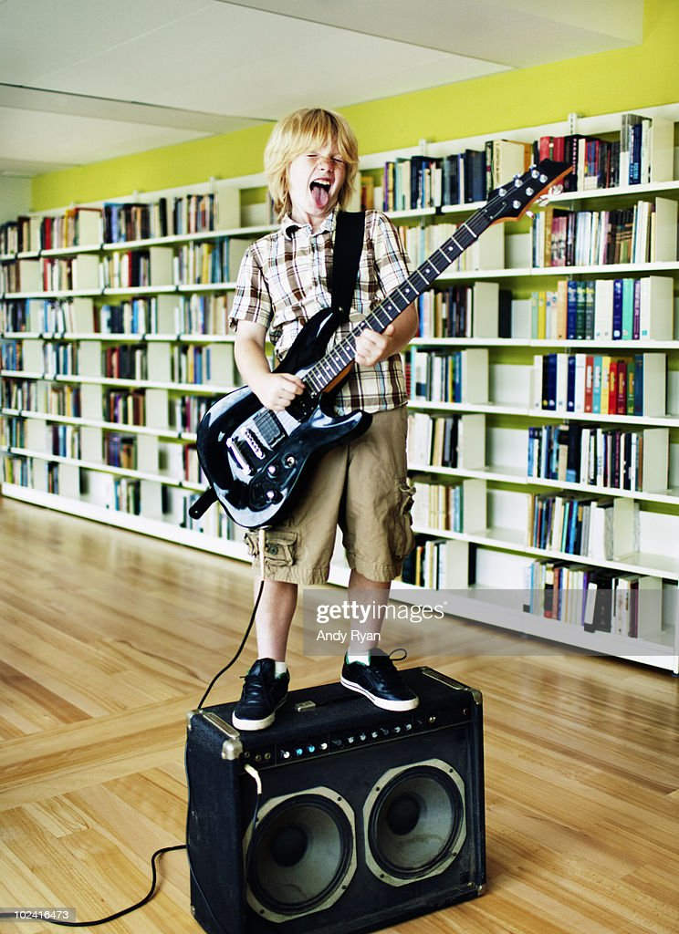 boy playing electric guitar in library : Stock Photo