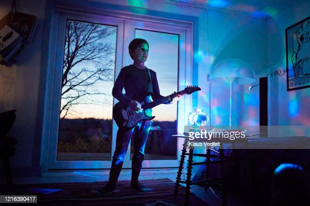 boy playing electric guitar in living room with neon light - musical equipment stock pictures, royalty-free photos & images
