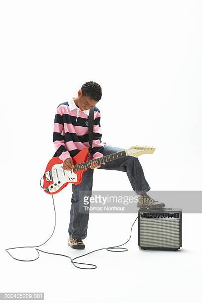 boy (9-11) playing electric guitar, resting foot on amplifier - electric guitar stock pictures, royalty-free photos & images