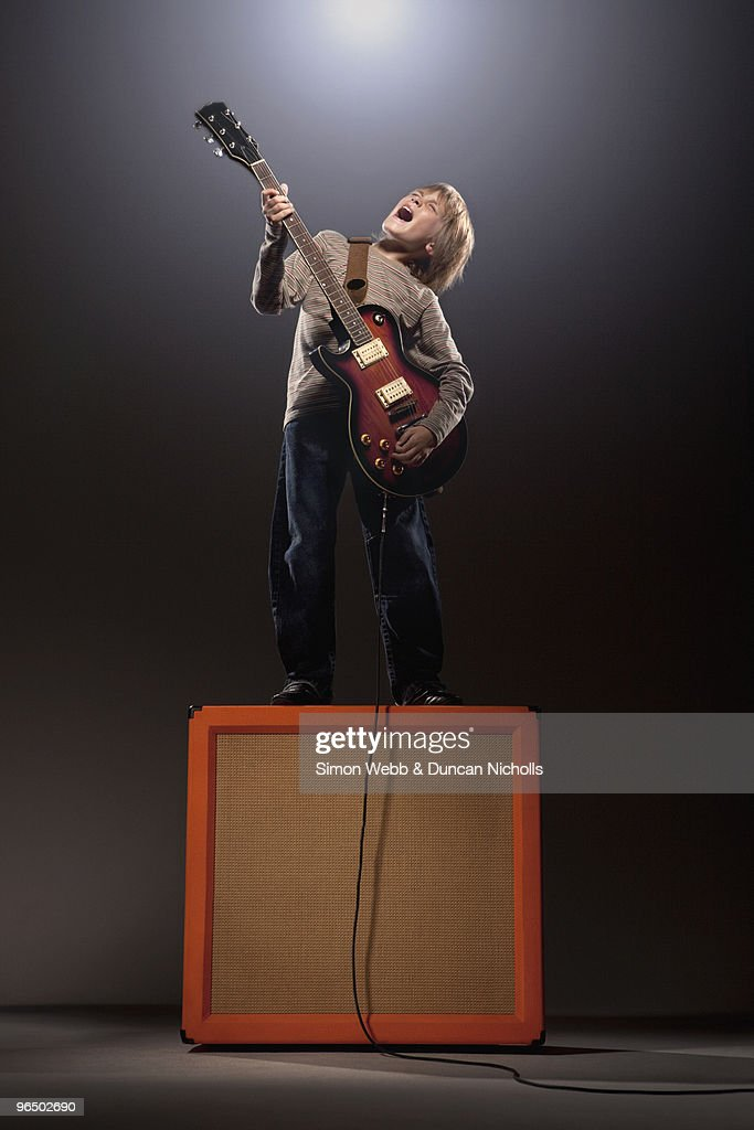 Boy playing electric guitar standing on speaker : Stock Photo