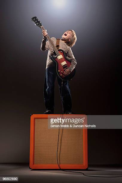 Boy playing electric guitar standing on speaker