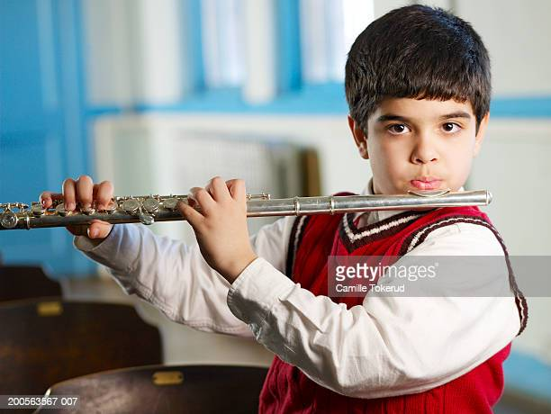 Boy (6-7) playing flute in classroom, portrait