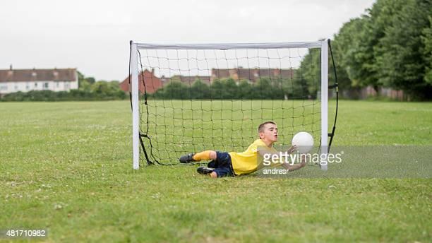 Boy playing football and saving a goal