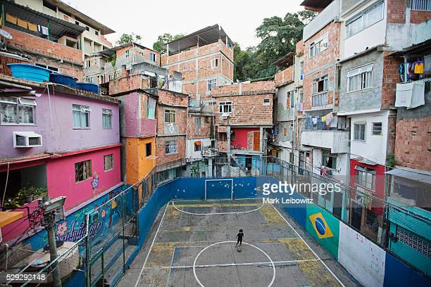 Boy (8-9) playing football in city playing field, Rio de Janeiro, Brazil