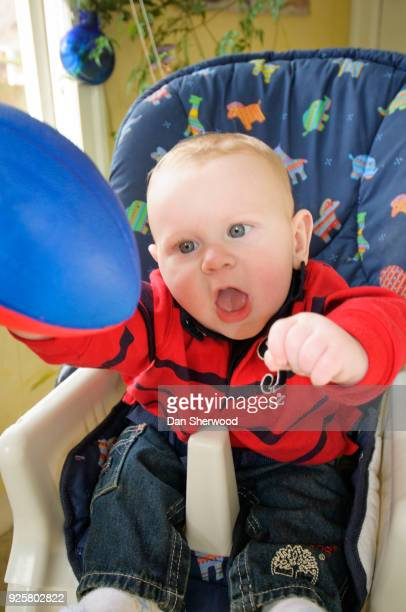 Boy Playing Football in his High Chair on Valentine's Day 2010