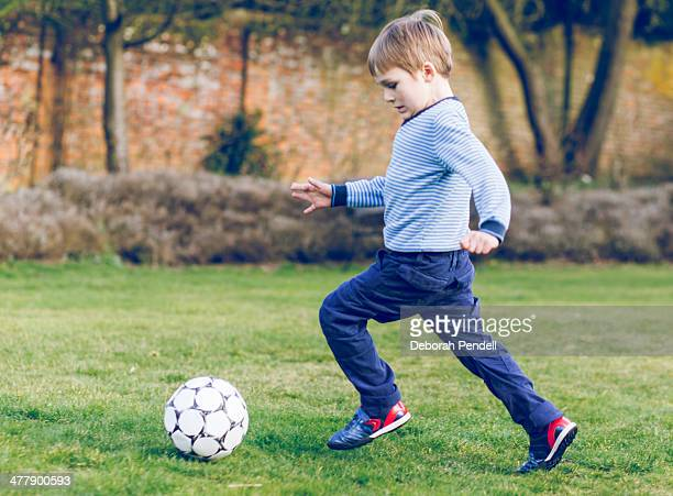 Boy playing football in the garden