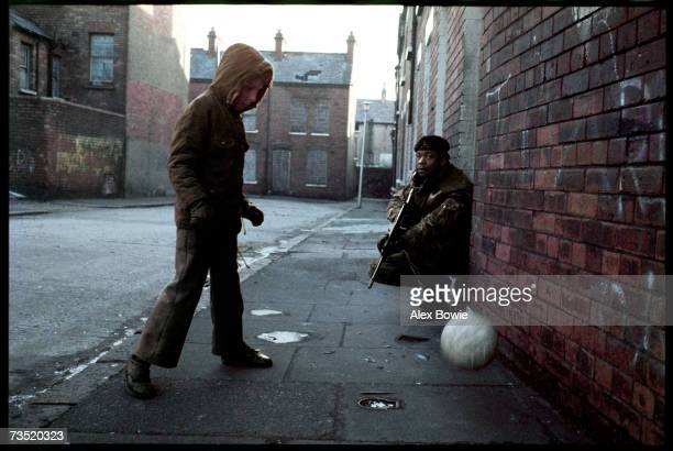 A protestant boy playing football on a street in the sectarian divide of north Belfast where a British soldier is on patrol 21st January 1972
