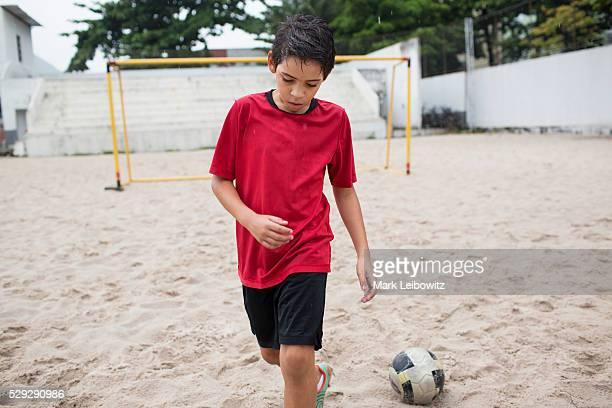 Boy (10-12) playing football on sand