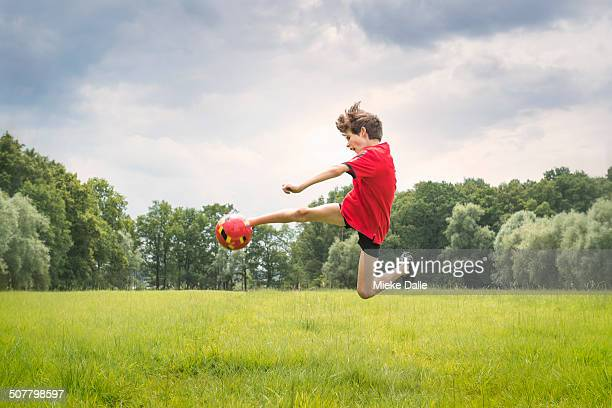 boy playing football - kicking stock pictures, royalty-free photos & images