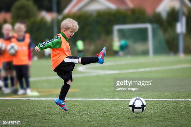boy playing football - kindertijd stockfoto's en -beelden