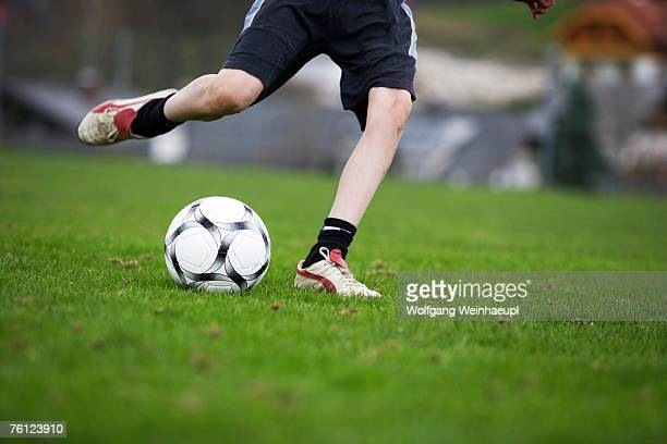 boy (12-13), playing football - kicking stock pictures, royalty-free photos & images
