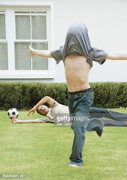boy (9-11) playing football with father running with t-shirt over head - marcar términos deportivos fotografías e imágenes de stock