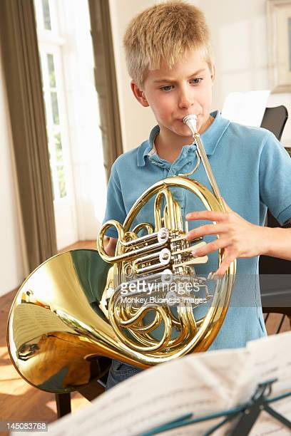 Boy playing French horn at home