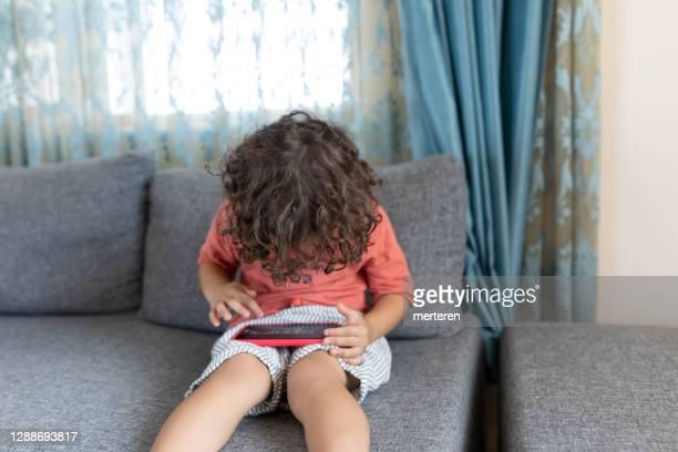 menino jogando no celular em casa - cartoon characters with curly hair - fotografias e filmes do acervo