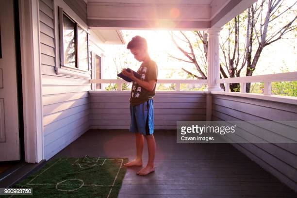 Boy playing game on tablet computer at porch