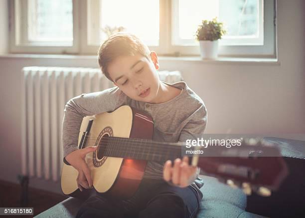 Junge spielt Gitarre wie zu Hause fühlen.